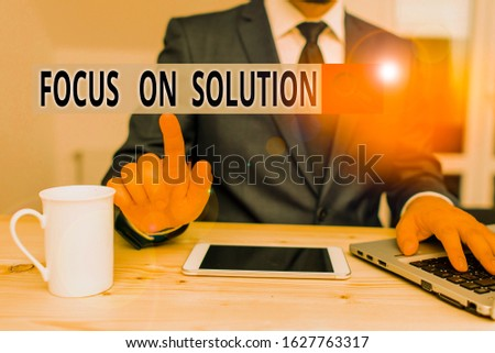 Handwriting text Focus On Solution. Concept meaning Give full attention on dealing answer of the situation Male human wear formal clothes present presentation use hi tech smartphone. #1627763317