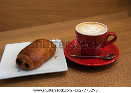 a cup of coffee and a pastry in a shop or diner setting #1627775293