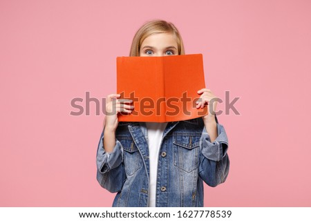 Little blonde kid girl 12-13 years old in denim jacket posing isolated on pastel pink background children portrait. Childhood lifestyle concept. Mock up copy space. Covering face with book, notebook Royalty-Free Stock Photo #1627778539