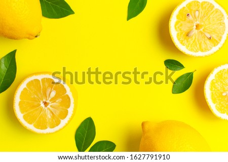 Creative background with fresh lemons and green leaves on bright yellow background. Top view flat lay copy space. Lemon fruit citrus minimal concept vitamin C. Composition with whole, slices of lemons #1627791910
