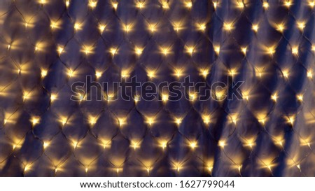 Festive garland with numerous yellow lights glows in the dark on the background. Colorful and magical decoration for the holidays #1627799044