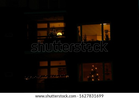Garland decorated windows at night of a multi-storey residential building in a residential area of the city #1627831699