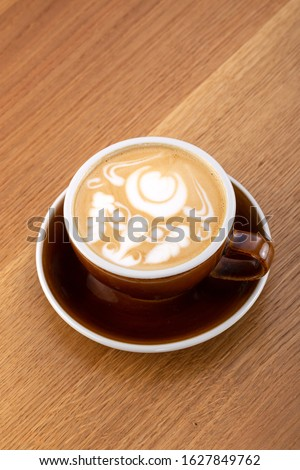 a cup of hot latte coffee on aged brown wood, heart shape latte art, coffee lover concept. Hot coffee on a wooden table. a cup of hot coffee latte, beautiful latte art #1627849762
