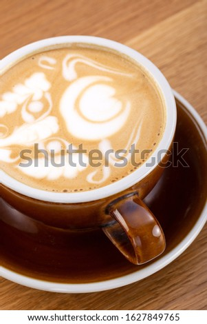 a cup of hot latte coffee on aged brown wood, heart shape latte art, coffee lover concept. Hot coffee on a wooden table. a cup of hot coffee latte, beautiful latte art #1627849765