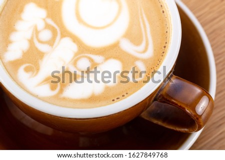 a cup of hot latte coffee on aged brown wood, heart shape latte art, coffee lover concept. Hot coffee on a wooden table. a cup of hot coffee latte, beautiful latte art #1627849768