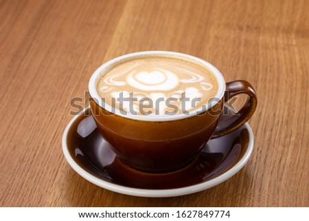 a cup of hot latte coffee on aged brown wood, heart shape latte art, coffee lover concept. Hot coffee on a wooden table. a cup of hot coffee latte, beautiful latte art #1627849774