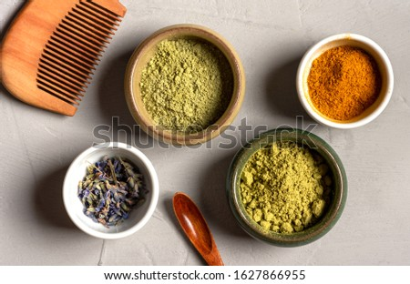 Ayurvedic hair care products. Henna, turmeric and neem powder in bowls on a grey background, top view. Natural care and hair coloring.