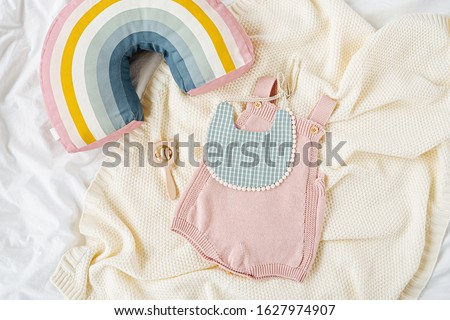Pink bodysuit and  bib on knitted blanket. Set of  kids clothes and accessories  on bed. Fashion newborn. Flat lay, top view #1627974907
