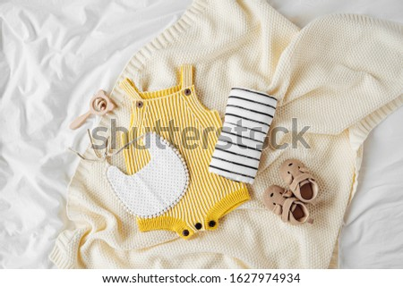 Yellow bodysuit, bib, baby boots and toy on knitted blanket. Set of  kids clothes and accessories  on bed. Fashion newborn. Flat lay, top view #1627974934