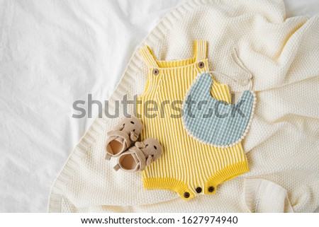 Yellow bodysuit, bib, baby boots and toy on knitted blanket. Set of  kids clothes and accessories  on bed. Fashion newborn. Flat lay, top view #1627974940