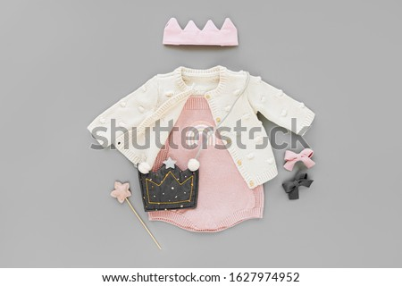Pink bodysuit with knitted jumper, kids handbag, cotton crown and magic wand. Set of  baby clothes and accessories on gray background. Fashion childs outfit. Flat lay, top view #1627974952
