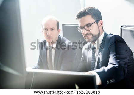 Image of two thoughtful businessmen looking at data on multiple computer screens, solving business issue at business meeting in modern corporate office. Business success concept. #1628003818