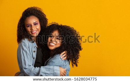 Two beautiful afro friends hugged, concept of best friends and sisters.