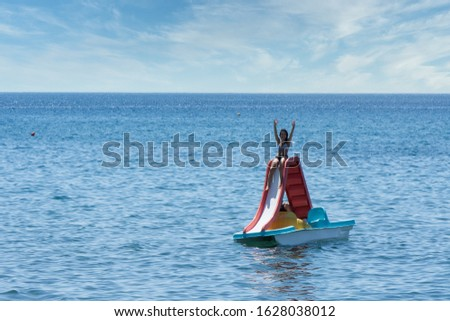 Teen in bathing suit sitting with hands up in the air on paddleboat with slide at beach in Eressos, Lesvos Greece #1628038012