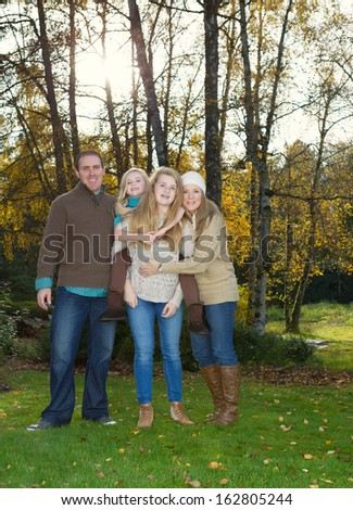 Vertical photo of family standing in front of trees, with sunlight coming through, during a nice day in the fall season