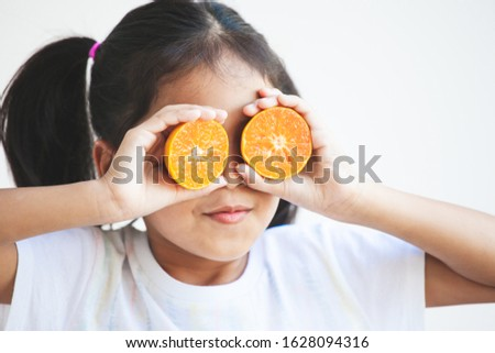 Cute asian child girl holding fresh oranges covering her eyes. Kid having fun to play with fresh fruit. #1628094316