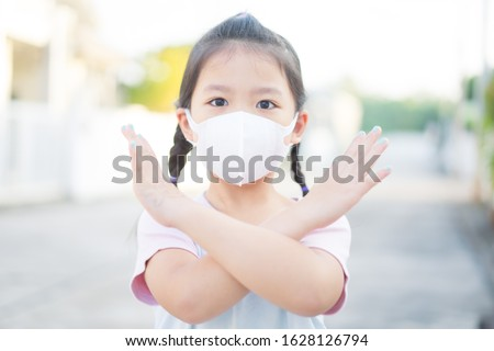 Coronavirus and Air pollution pm2.5 concept.Little chinese girl wearing mask for protect pm2.5 and show stop hands gesture for stop corona virus outbreak.Wuhan coronavirus and epidemic virus symptoms. #1628126794