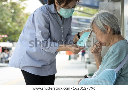 Asian female daughter is care, help, wearing face mask protection for senior mother,woman and elderly with medical mask because of air pollution,Coronavirus,Wuhan Corona virus 2019-nCoV,Covid-19, SARS Royalty-Free Stock Photo #1628127796