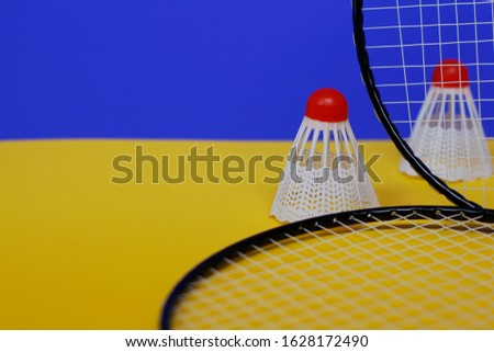 Badminton. Two shuttlecocks and two badminton racket. The colored background is blue and yellow. Idea for a magazine. #1628172490