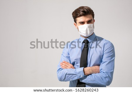 is time to protect all the time. elegant man wearing a mouth protection to prevent getting sick at work or on the way to work #1628260243