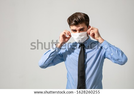 is time to protect all the time. elegant man wearing a mouth protection to prevent getting sick at work or on the way to work #1628260255