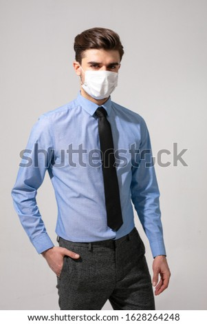 outfit with virus protection. elegant man with tie wearing a mouth protection against contagious diseases #1628264248