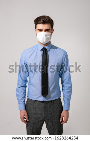 outfit with virus protection. elegant man with tie wearing a mouth protection against contagious diseases #1628264254