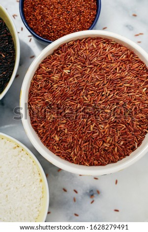 Ceramic bowls filled with a variety of grain and rice including red quinoa, red rice, black rice, and white rice on a marble top.   #1628279491