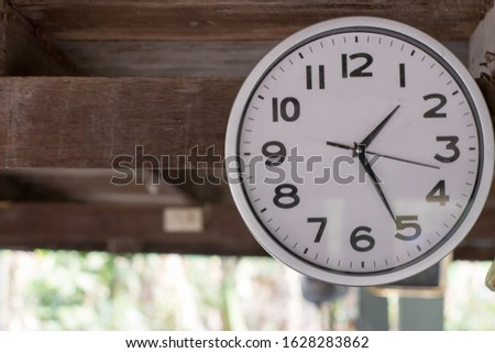 A wall clock that was hung at an antique wooden house #1628283862