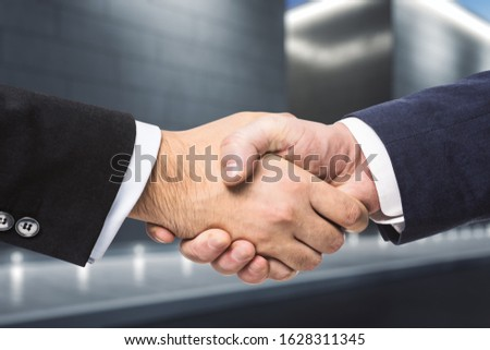 Two businessmen shake hands in the evening on a abstract exterior backgrond. Insider concept #1628311345