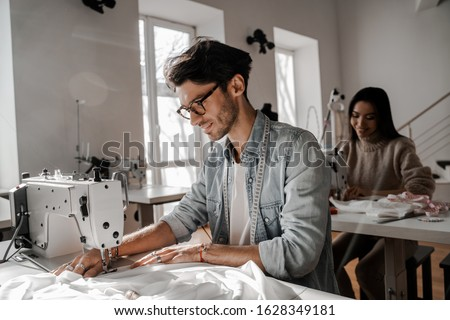 Focused on the sewing process tailors sit sewing at their sewing machines. Sewing, design work, tailoring studio, tailor, designer clothes, manufactory, in the process of creative development #1628349181