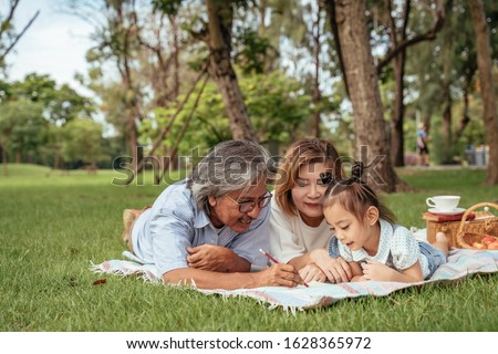 Grandmother,Grandfather and grand daughter enjoying sunny garden holiday together, outdoors space, leisure lifestyle,happy teaching with flare light sky in park. #1628365972