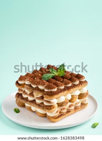 Tiramisu , italian layered dessert with mascarpone cream, decorated with mint and cocoa powder.  #1628383498