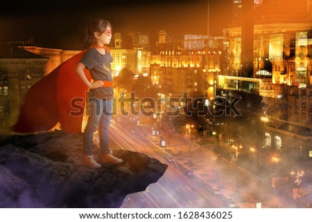 Cute little girl dressed as superhero looking at night city from rock