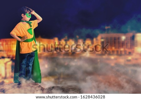 Cute little boy dressed as superhero looking at night city from rock