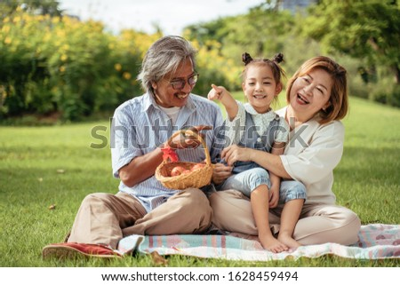 Grandmother,Grandfather and grand daughter enjoying sunny garden holiday together, outdoors space, leisure lifestyle,happy teaching with flare light sky in park. #1628459494