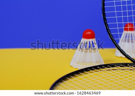 Badminton. Two shuttlecocks and two badminton racket. The colored background is blue and yellow. Idea for a magazine. #1628463469