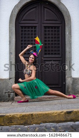 Happy woman dancing in the carnival of Brazil with the typical scenario of Olinda. Frevo dancing.