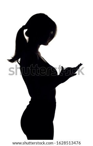 silhouette figure of girl in sportswear on white isolated background, woman counts calories on smartphone, healthy lifestyle concept, dieting and sports Royalty-Free Stock Photo #1628513476
