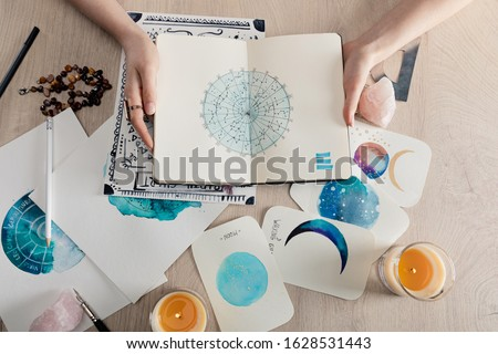 Top view of astrologer holding notebook with watercolor drawings and zodiac signs on cards on table #1628531443