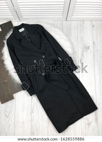 Black women`s double-breasted coat on a white wooden background #1628559886