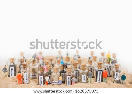 Glass test-tube with sand of different summer vacation destinations. Located in sand with small people figures. #1628575075