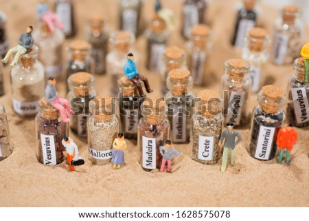 Glass test-tube with sand of different summer vacation destinations. Located in sand with small people figures. #1628575078