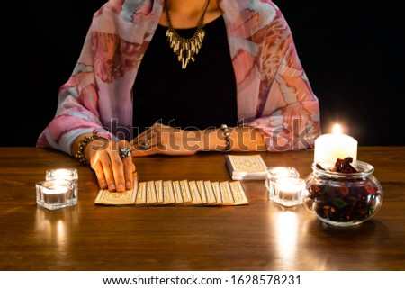 Tarot reader picking tarot cards.Tarot cards face down on table near burning candles.Tarot reader or Fortune teller reading and forecasting concept. #1628578231