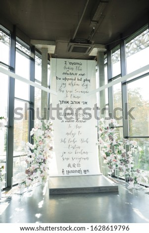 """The photo zone is decorated with flowers and parchment with the words """"I love you"""" in different languages of the world. Wedding ceremony. Valentine's Day"""