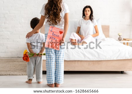 back view of brother and sister holding flowers and i love you mom card, and surprised woman sitting in bed