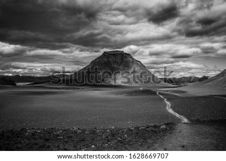 Wonderful landscape in Iceland (Europe) Travel to the reserve. Northern nature, beautiful views. Lonely volcano among a lava field. Cloudy weather. Black and white art.