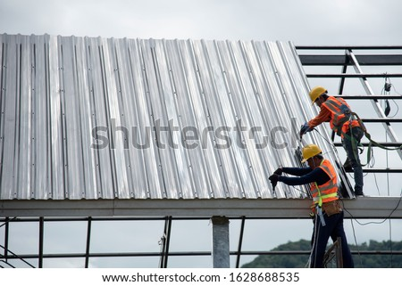 2 workers for construction, installing metal roofing tools, sheet metal New electric drill tool used on a new roof with metal sheets. #1628688535