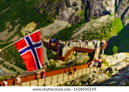 Trollstigen mountain road landscape in Norway, Europe. Norwegian flag waving and many tourists people on viewing platform in background. National tourist route. #1628690149