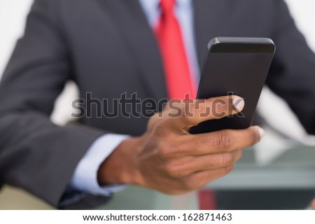 Close up mid section of a well dressed young businessman text messaging #162871463